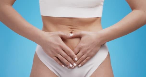 Schnappschuss einer Frau, die unter Bauchschmerzen leidet, ihren schmerzenden Bauch berührt, Nahaufnahme, blauer Studiohintergrund