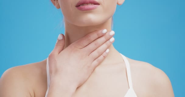 Young unrecognizable woman suffering from sore throat, touching her neck, blue background, close up
