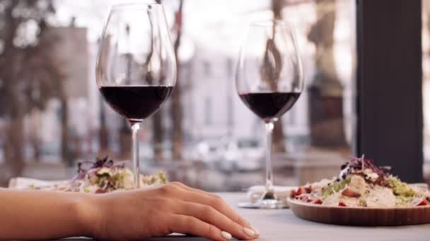 Mužská ruka přechází k ženě na obědovém stole a dotýká se jí během romantického rande v kavárně, zblízka, zpomalený pohyb