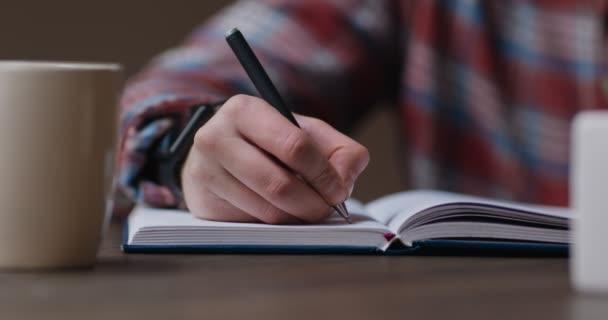 Közelkép egy férfiról, aki jegyzetfüzetbe vagy naplóba ír, otthon ül az asztalnál kávéval a kezében.