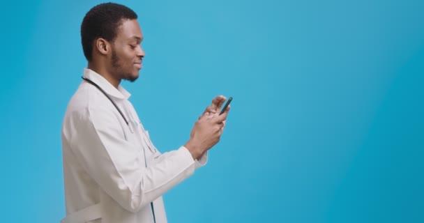 Profil Portrait eines afrikanisch-amerikanischen Doktors, der mit einem Patienten auf dem Handy chattet, blauer Hintergrund mit leerem Raum