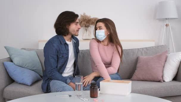 Junger Mann versucht seine Freundin zu küssen, kranke Frau in Schutzmaske hält ihn auf, sitzt zu Hause auf Couch