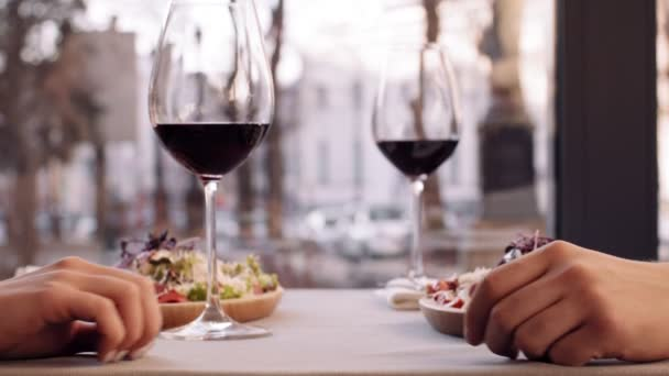 Close up shot of romantic couple holding hands in cafe, dating with wine glasses, slow motion