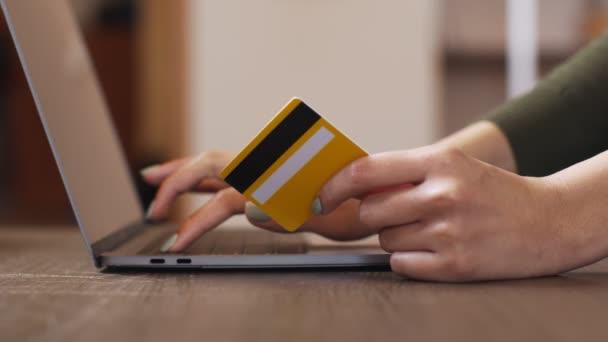 Nahaufnahme einer Frau, die Passwort eingibt und Kreditkarte hält, Online-Einkauf von zu Hause aus, Zeitlupe
