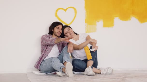 Mladý pár v lásce dělat domácí opravy společně, sedí na podlaze a diskutovat o interiéru design, zpomalení