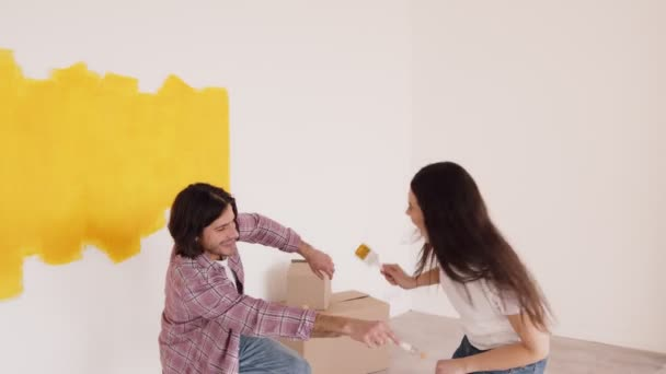 Funny repair. Young married man and woman painting walls at home, trying to paint each other, laughing and having fun