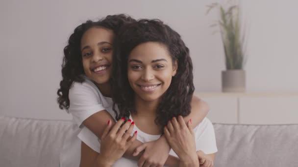 Detailní záběr portrét roztomilé šťastné africké americké dívky objímající svou matku doma, usmívající se na kameru
