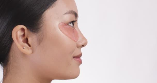 Mladá asijská dáma nosí gel náplasti při pohledu stranou a usmívající se, bílé studio pozadí s volným místem