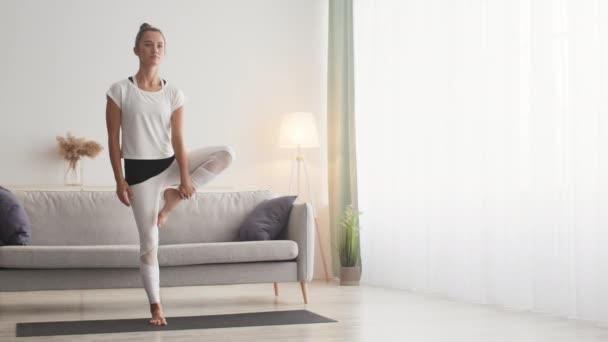 Trénink jógy doma. Mladá žena medituje doma, cvičí stromovou asanu, ruce v namaste gestu, prázdný prostor
