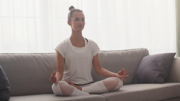 Ranní trénink. Mladá mírumilovná dáma meditující, sedící v lotosové pozici na gauči, držící se za ruce v mudře