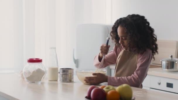 Wenig konzentriertes afrikanisch-amerikanisches Mädchen bereitet Backen zu Hause vor, mixt Zutaten in Schüssel mit Schneebesen in der Küche