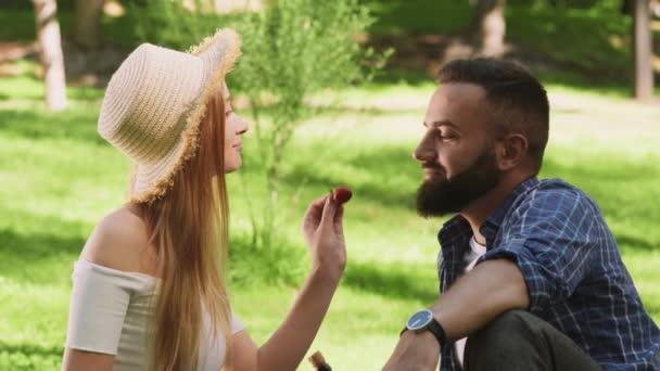 Láska hry. Milý pár odpočívá v parku, žena krmí muže čerstvými jahodami a líbá ho