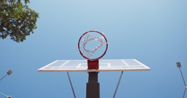 Untere Ansicht des schwarzen Basketballballs, der auf dem Streetballfeld in eine Schleife fällt, Zeitlupe, Spieler schießt ein Tor