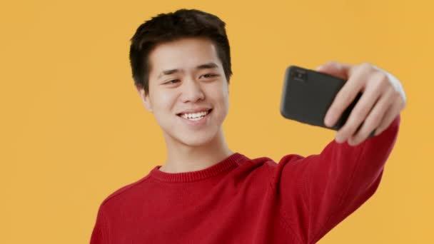 Asijské chlap dělat selfie na smartphone pózování přes žluté pozadí