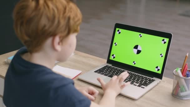 Online kids development. Little boy using online educational platform, working on laptop with green chroma key screen