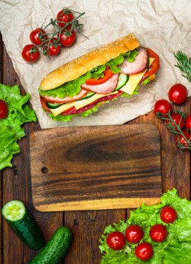 Food design - sandwich with meat and vegetables on wood