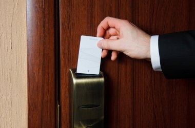 Hand inserting card into electronic lock in hotel