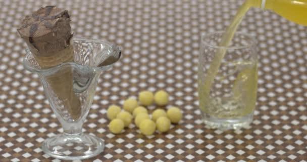 nalévání limonády ve skle vedle zmrzliny a bonbónů na stůl, zpomalení