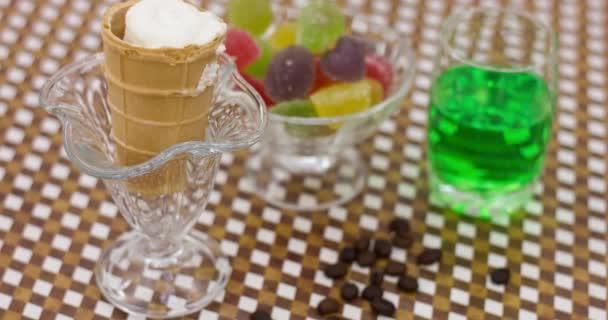 Fagylalt, ízletes édességek és egy pohár limonádé a konyhaasztalon. Gyerekek születésnapi ünnepség koncepció