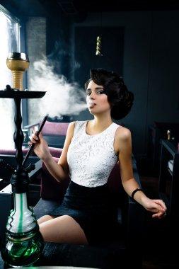 woman smokes a hookah in cafe
