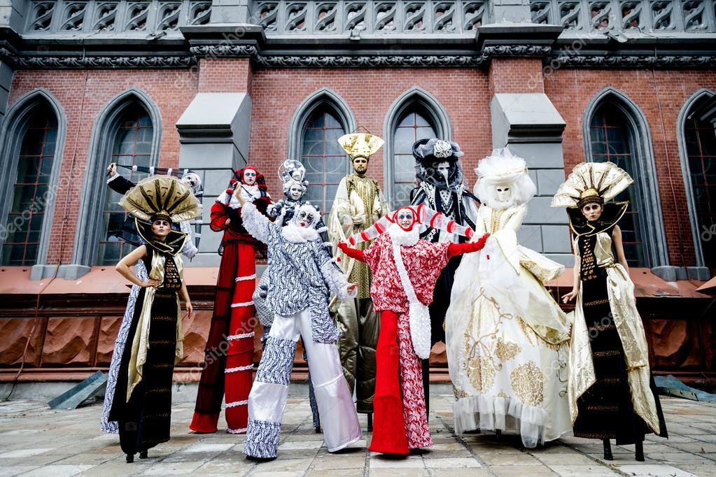 Colorful stiltwalkers in a variety of carnival costumes