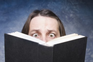 Mature woman being focused and hooked by book.