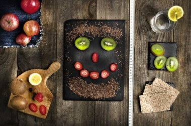 Funny face arranged from linseed, kiwi and strawberry on black stone. Healthy food, diet conception. Fresh fruits on wooden background.