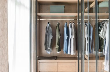 shirts and suite hanging on rail in wooden wardrobe
