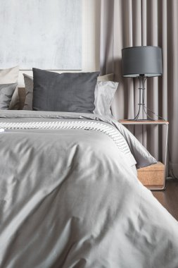grey pillow on white bed in modern bedroom with black lamp