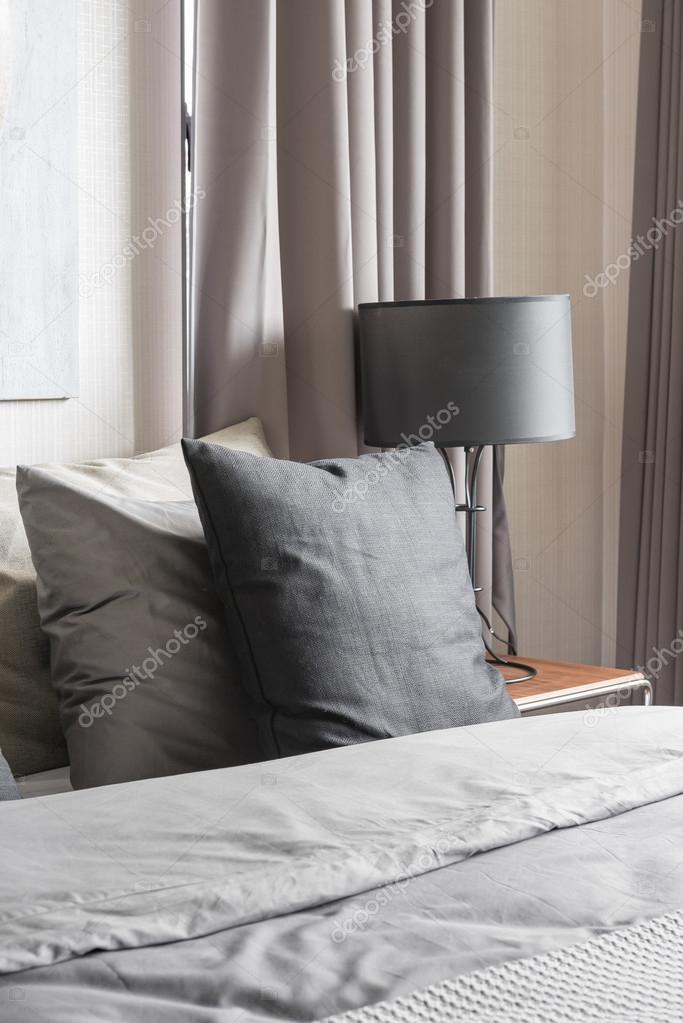 Grigio cuscino sul letto bianco in camera da letto moderna ...