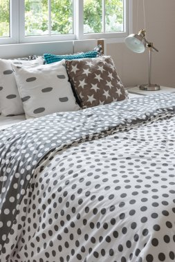 Dot pattern blanket on modern bed with lamp in bedroom