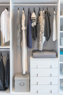 clothes hanging in modern white wardrobe