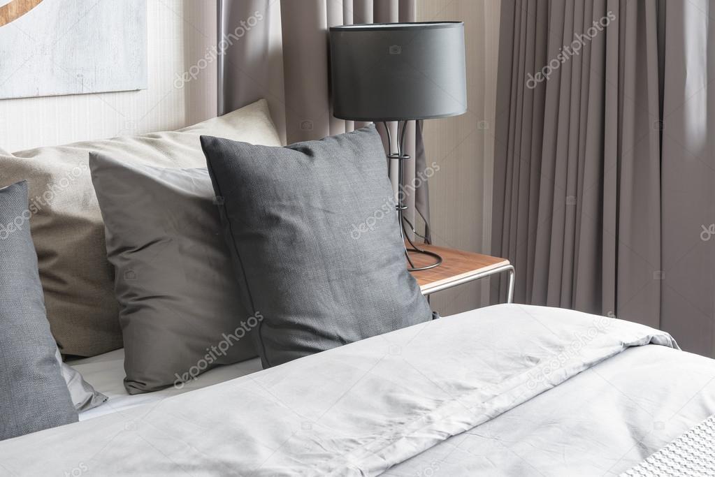 Grijze Slaapkamer Lamp : Grijs kussen op witte bed in moderne slaapkamer met zwarte lamp