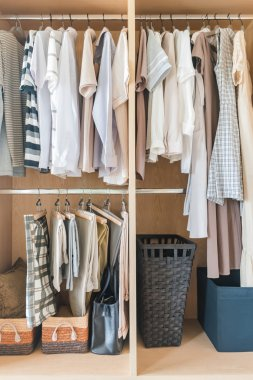 clothes and dress hanging on rail in wooden closet