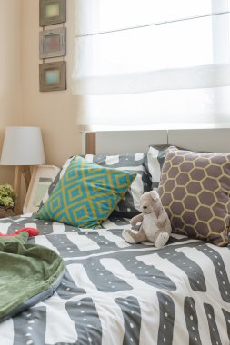 kid's bedroom with colorful pillows on white bed and modern lamp