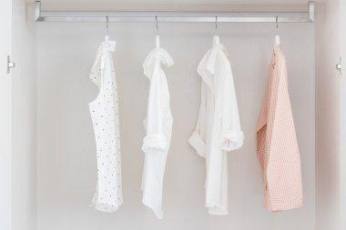 shirts hanging on rail in white wooden wardrobe
