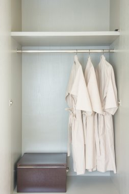 bathrobe hanging on rail in white wooden wardrobe