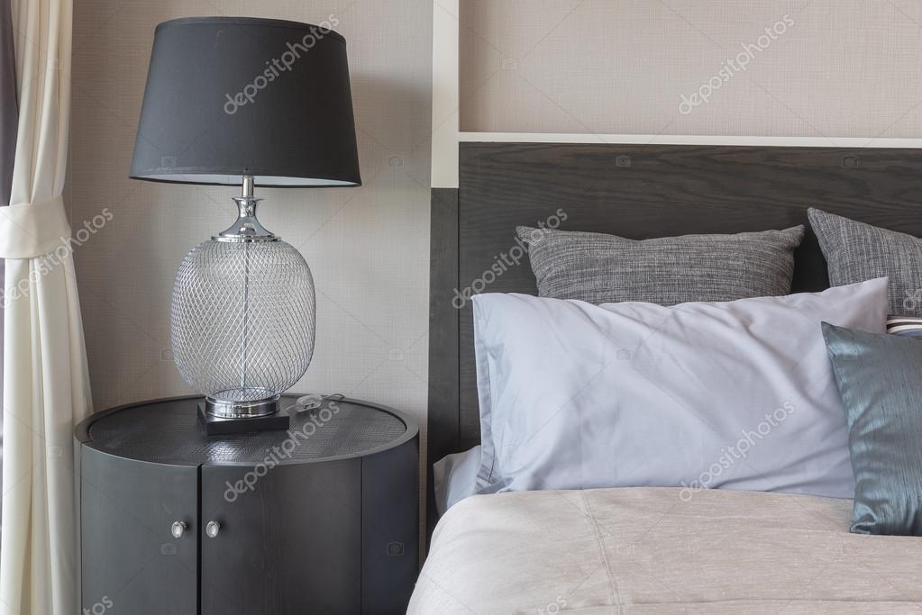 Kussens op bed en luxe zwarte lamp stijl aan houten tafel kant