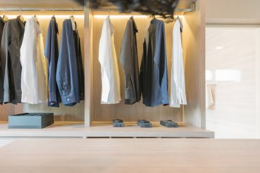 clothes hanging in wooden walk in closet