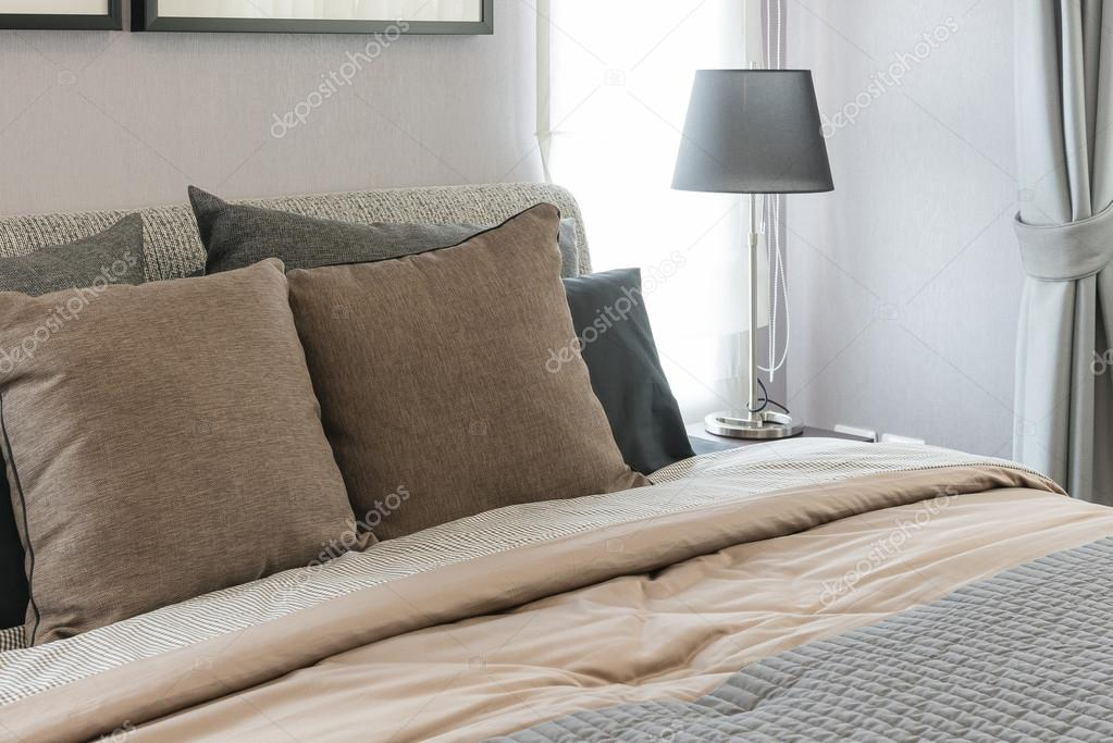 marroni cuscini sul letto con lampada nera in camera da ...