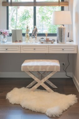 White dressing table and chair with women's accesories with vase