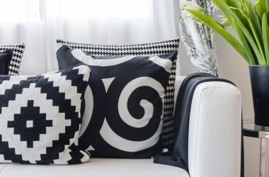 black and white pattern pillows on white sofa