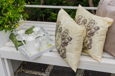 tray of tea set and pillows on white bench