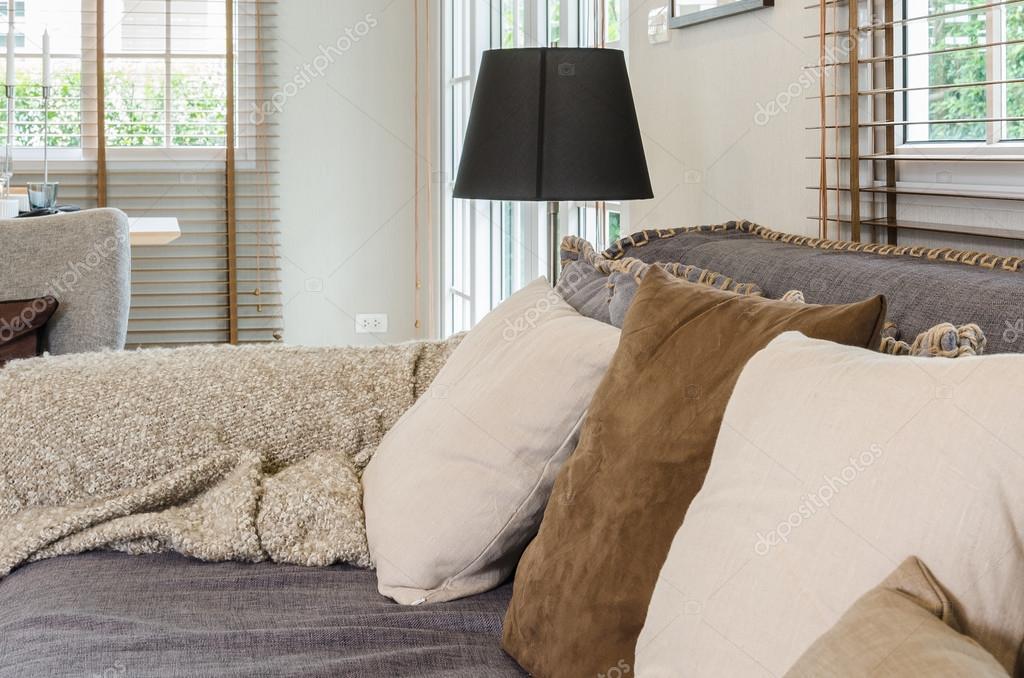 woonkamer design met kussens op grijze bank en zwarte lamp ...
