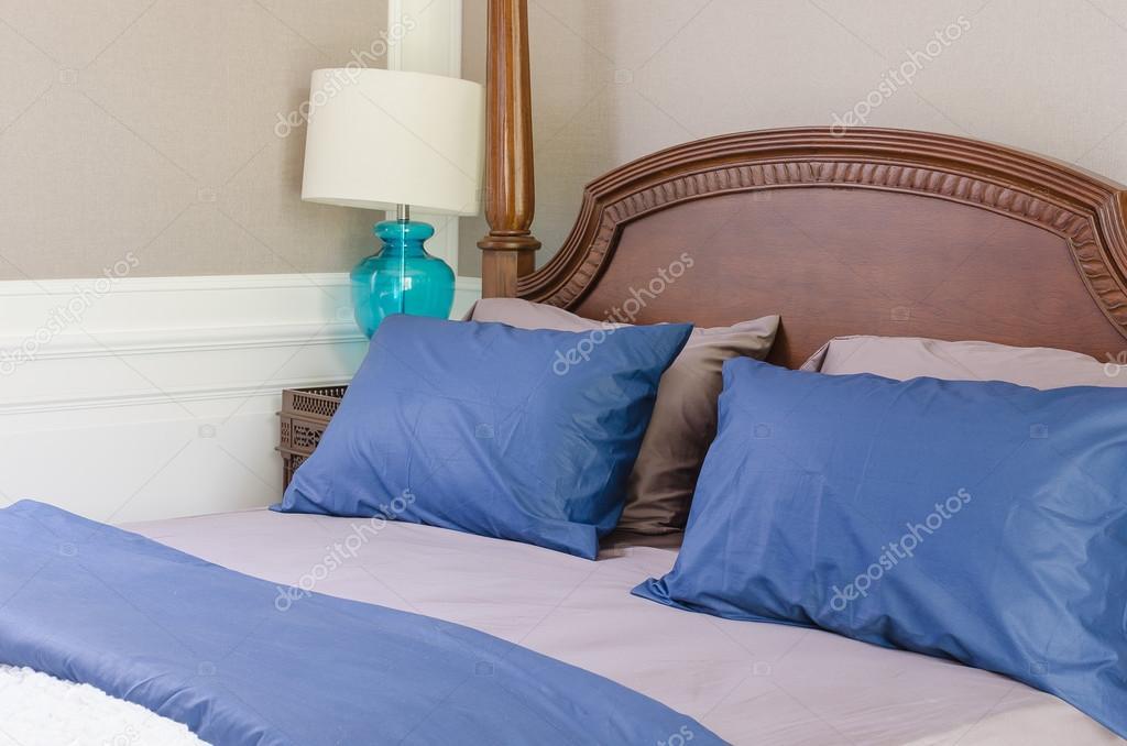 Kussens Blauw Grijs : Blauw en grijs kussens op klassieke houten bed met moderne lamp