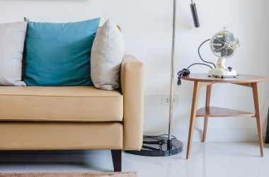 Modern sofa with pillows and classical electric fan