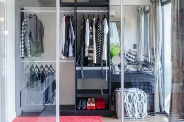Closet with glass partition in bedroom
