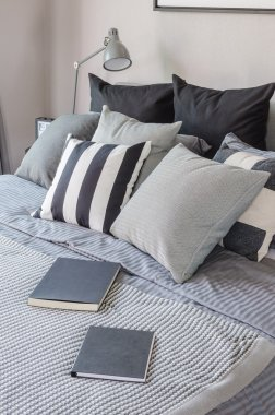 black books on black and white bed in bedroom