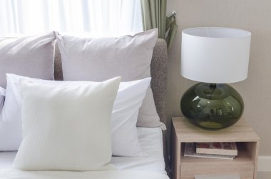 white pillows on modern white bed with modern lamp