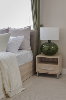 White pillows on bed with modern white lamp on wooden table side